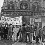 """December 25th, 1985. Members of 'SOS Racisme' and the French anti-apartheid movement, including current Socialist party chairman Harlem Désir, gather in front of Notre Dame cathedral in Paris for a Christmas Day rally. Their banners read """"No to apartheid"""" and """"Free Mandela.""""Photo: Michel Clement"""