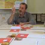 """<strong>Etre et Avoir - To Be and To Have – (2002).</strong> A slow, quiet documentary about a tiny school in a small rural village in Puy-de-Dôme, central France. Hardly the classic recipe for an international success, but the calm dedication of teacher Georges Lopez, the cosy agrarian setting, and the spontaneous sweetness of the young kids gives this film a timeless feel. 'To Be and to Have' is a victory for the simple joys of childhood and should be prescribed by doctors to treat the blues.Photo: Teacher Georges Lopez holds a card saying """"Friend."""" Gerd81/Youtube"""