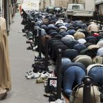 Praying in the street at the Goute d'OrPhoto: Martin Parr