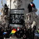 """A sign that reads """"I think therefore I am"""" is hung at the Place de la Republique as people gather with their national flags.Photo: Joel Saget/AFP"""