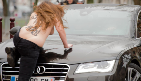 Topless protesters jump on Strauss-Kahn's car