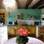 The colourful kitchen has kept most of its original features, including oak beams and decorative 'Colombages'(half-timbering). It is fully equipped and ready to welcome dinner guests in a large sitting area overlooking the garden.Photo: Leggett