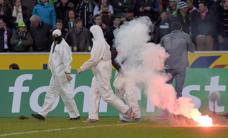 Köln ultras storm the pitch after local derby. Photo: DPA