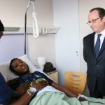French president visits man 'raped with police baton' as suburban tensions simmer
