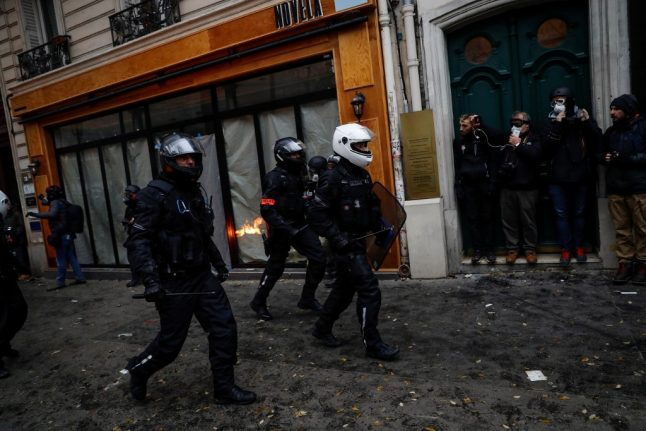 Paris police use tear gas to disperse rioters as tens of thousands protest