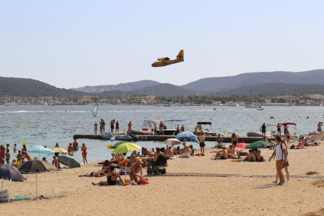 Beachgoers watch as a Canadair firefighting plane descends to the sea in the bay of Saint-Tropez to collect water to fight a nearby forest fire