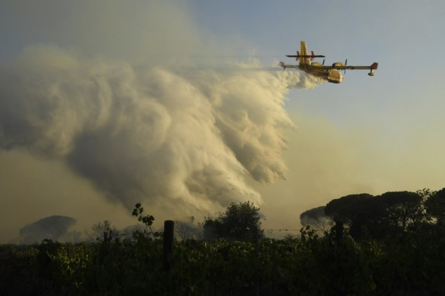 A Canadair firefighting aircraft dropping tonnes of water on a forest fire in southern France