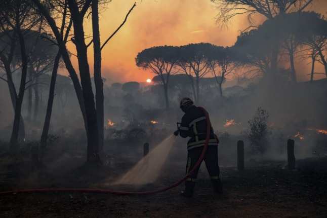 The silhouette of a firefighter using a hose to put out flames from a forest fire in southern France against a setting sun