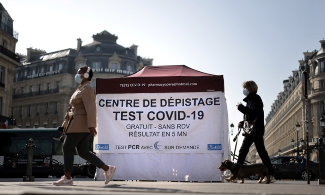 People walking past a pop-up Covid test centre at the Opera square in Paris. Tests were previously free for residents.