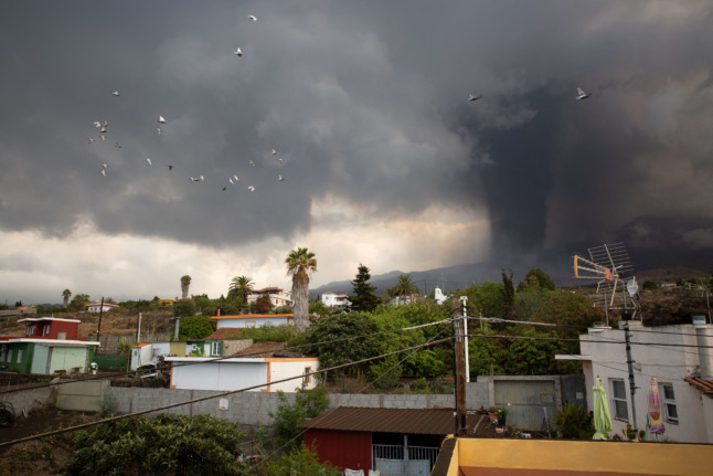 A column of smoke and pyroclastic materials spewed by the Cumbre Vieja volcano is seen from the neighbourhood of Todoque in Los Llanos de Aridane on the Canary island of La Palma in September 24, 2021 (Photo by DESIREE MARTIN / AFP)